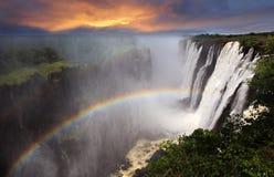 Victoria Falls solnedgång med regnbågen, Zambia Arkivbild