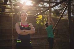 Det beslutsamma kvinnaanseendet med armar korsade under hinderkurs arkivbild