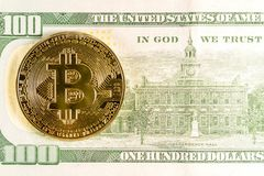 Det Bitcoin myntet ligger på en 100 dollar sedelnärbild royaltyfri bild