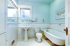 Det blåa antika eleganta badrummet med vit badar. Arkivfoton