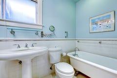 Det blåa antika eleganta badrummet med vit badar. arkivbild
