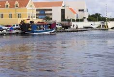 Det blåa fartyget förtöjde bak iconic färgrika byggnader av Curacao royaltyfri bild