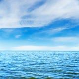 Det blåa havet och godan fördunklar i himmel Arkivbild