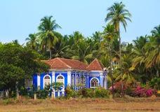 Det blåa huset i kokosnöten gömma i handflatan dungen i Goa Royaltyfria Bilder