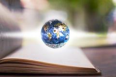 Det blåa jordklotet som göras av stål på inbunden bokboken utbildning och ind Royaltyfria Bilder