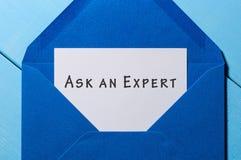 Det blåa kuvertet med bokstaven och anmärkningen FRÅGAR EN EXPERT royaltyfria foton
