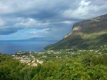 Det blåa och blåa havet, stad, vaggar under himlen med moln och utsmyckade skuggor på berget, Maratea, Basilicata, Italien royaltyfria bilder