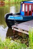 Det blåa och röda kanalfartyget förtöjde i framåt & Clyde Canal, Scotl Arkivfoto