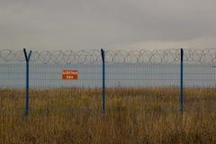 Det blåa staketet med försett med en hulling - binda i fältet royaltyfria foton