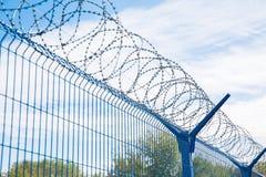 Det blåa staketet med försett med en hulling - binda på bakgrund för blå himmel farligt område arkivbilder
