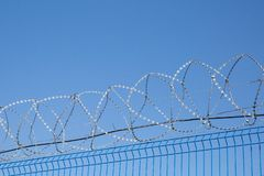 Det blåa staketet med försett med en hulling - binda på bakgrund för blå himmel farligt område arkivfoton