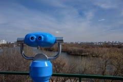 Det blåa teleskopet av observationsdäcket parkerar in Kolomenskoye med sikt av vårskogen, den Moskva floden och staden på bakgrun Royaltyfri Bild