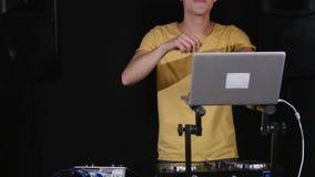 Det blandande musikanseendet för dj på hans däck, dans med hans hörlurar runt om hans hals stock video