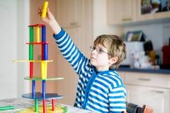 Det blonda barnet med exponeringsglas som spelar med massor av färgrika träkvarter, spelar inomhus Aktiv rolig ungepojke som har  royaltyfri fotografi