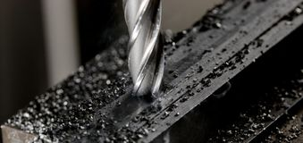 Det Bridgeport CNC-slutet maler fullföljande av en bunt av stålplattan med metallarkiveringschiper omkring arkivbild