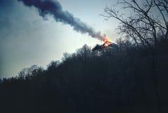 Det brinnande huset i bergen Royaltyfria Bilder