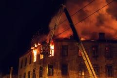 Det brinnande huset på natten, taket av byggnad i flammor av brand och rök, brandman på kranen släcker brand med vatten från slan royaltyfri foto