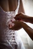 Det brudtärnabandet snör åt på baksidan av en bröllopsklänning Fotografering för Bildbyråer
