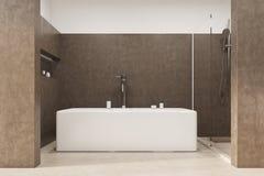 Det bruna badrummet med ett vinkelformigt badar Arkivfoto