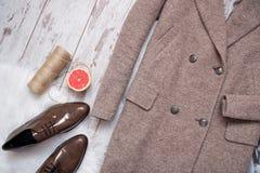 Det bruna laget och bruna skor för patenterat läder på en vit päls, grapefrukt och tvinnar, träbakgrund för begreppsframsida för  Royaltyfri Fotografi
