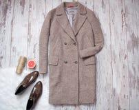 Det bruna laget och bruna skor för patenterat läder på en vit päls, grapefrukt och tvinnar, träbakgrund för begreppsframsida för  Arkivbilder