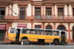 Det brutna gula bussstaget nära det gamla huset Arkivbild