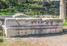 Det brutna långa marmorstycket av en byggnad som snidas med romerska bokstäver som beside staplas, fördärvar på anicent Corinth n arkivfoton