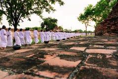 Det buddistiska folket går och ber runt om templet Royaltyfria Bilder