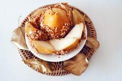 Det Caramelized päronet som doppades med jordnötter, dekorerade med guld- tjänstledigheter Royaltyfri Foto