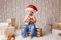 Det Caucasian barnet, i att dricka för den Santa Claus hatten, mjölkar från flaskan som firar jul royaltyfri foto