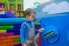 Det Caucasian barnet som spelar på lekplats in parkerar inomhus Fotografering för Bildbyråer