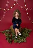 Det Chirstmas barnet på trädstubbe och sörjer trädfilialer, röd ferie Arkivbild