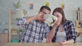 Det chockade unga paret ser in i en tom plånbok, begreppet, idén av brist av pengar stock video