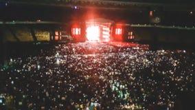 Det Defocused fotoet av stor stadion som är fullt av fans på, vaggar musikkonsert Perfekt bakgrund för att illustrera partiet, di arkivfoton