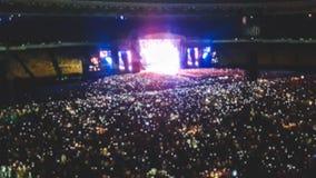 Det Defocused fotoet av stor stadion som ?r fullt av fans p?, vaggar musikkonsert Perfekt bakgrund f?r att illustrera partiet, di arkivfoton