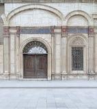 Det dekorerade fönstret och den träutsmyckade dörren över vit marmor dekorerade väggen Royaltyfri Foto