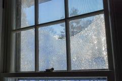 Det djupfrysta fönstret förser med rutor blå himmel för fönsterramlåset arkivbild