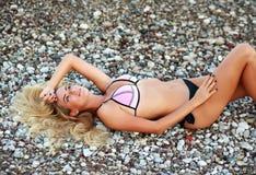 Det eftertänksamma sinnliga barnet bantar kvinnan som ligger på stranden i bikini Royaltyfria Bilder