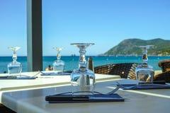 Det eleganta kafét med havssikt på franska Riviera väntar på gäster, tjänade som lunchtabellen med exponeringsglas, bordsservis o arkivbilder