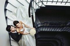 Det eleganta stilfulla barnet kopplar ihop den härliga bruden och brudgummen på sten Royaltyfri Fotografi