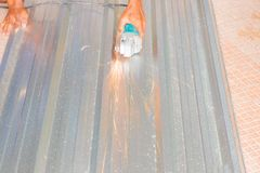 Det elektriska hjulet som maler på det bitande taket för metallarket i konstruktör, fungerar Välj fokusen med grunt djup av fälte Royaltyfri Bild