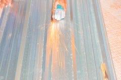 Det elektriska hjulet som maler på det bitande taket för metallarket i konstruktör, fungerar Välj fokusen med grunt djup av fälte Royaltyfria Foton