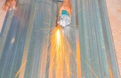 Det elektriska hjulet som maler på det bitande taket för metallarket i konstruktör, fungerar Välj fokusen med grunt djup av fälte Arkivbild