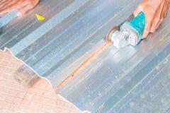Det elektriska hjulet som maler på det bitande taket för metallarket i konstruktör, fungerar Välj fokusen med grunt djup av fälte Royaltyfri Foto