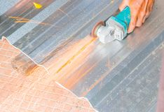 Det elektriska hjulet som maler på det bitande taket för metallarket i konstruktör, fungerar Välj fokusen med grunt djup av fälte Arkivbilder