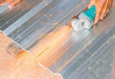 Det elektriska hjulet som maler på det bitande taket för metallarket i konstruktör, fungerar Välj fokusen med grunt djup av fälte Royaltyfri Fotografi