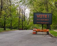 Det elektriska LEDDE tecknet på släpet, som säger, röstar Det är din rätt Det är din arbetsuppgift På en förorts- gata som fodras arkivbilder