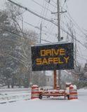 Det elektriska mobila tecknet för vägtrafik vid sidan av en dold väg för snö med att falla för snö, som säger, kör säkert arkivbilder