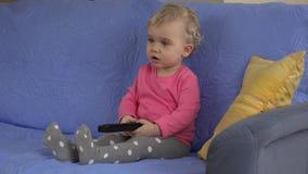 Det emotionella kvinnliga barnet med fjärrkontroll i händer koncentrerade på television lager videofilmer