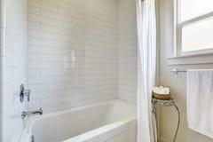 Det enkla badrummet med tegelplattaväggklippning och badet badar Arkivbilder